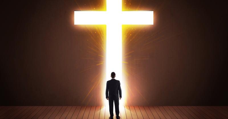 man in suit walking through lit doorway of Jesus cross