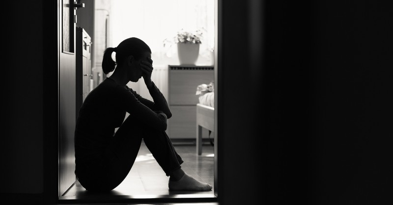Woman looking distressed sitting in her house