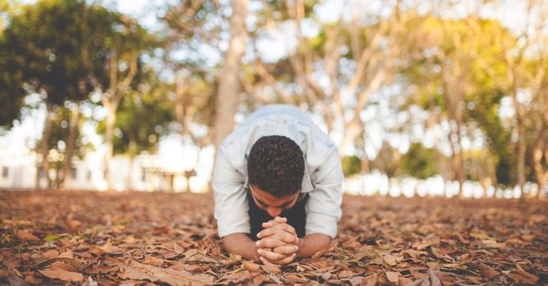 Man kneeling in the woods in prayer