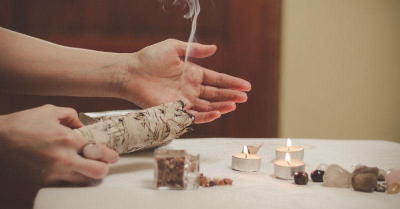 hands burning sage with tealight candles