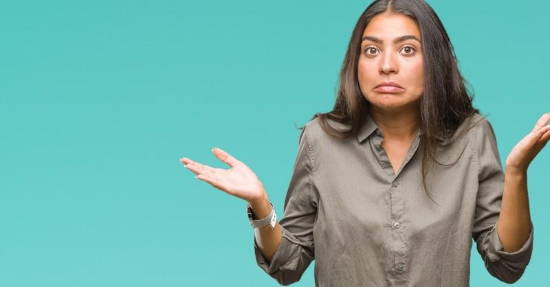 Confused woman shrugging shoulders