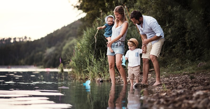 young family with little children playing with toy fishing poles by side of water