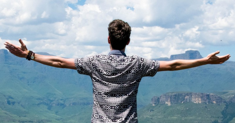 man with arms wide in praise and worship mountainscape