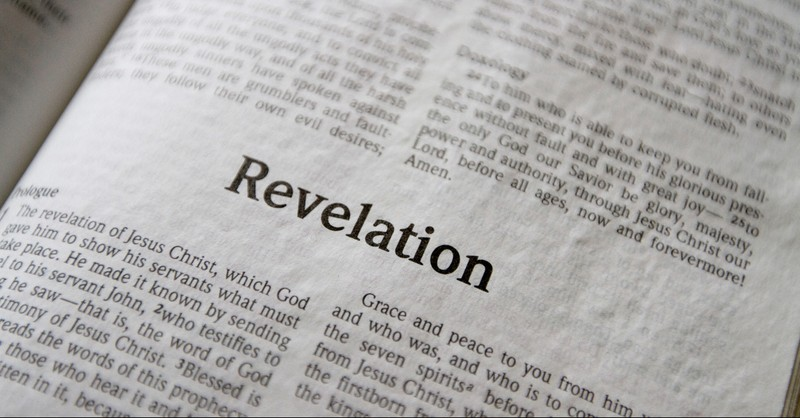Bible opened to Revelation, behold I stand at the door and knock