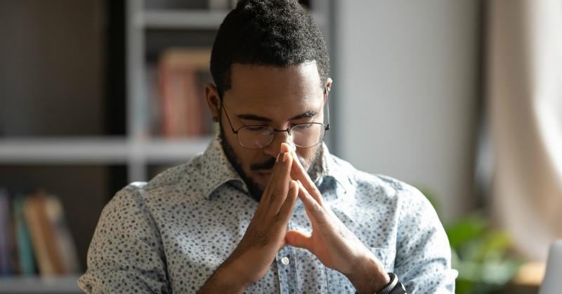 man at laptop praying