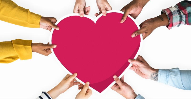 Multi-ethnic hands holding a heart