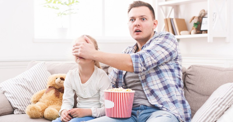 dad covering his daughter's eyes watching a movie