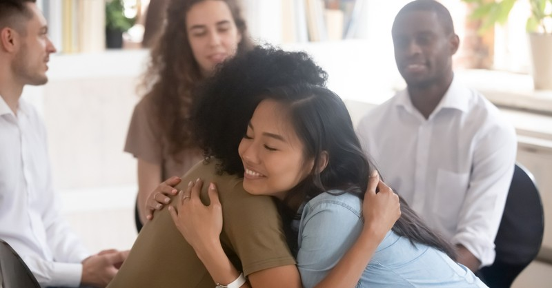 culturally diverse group of adults two hugging