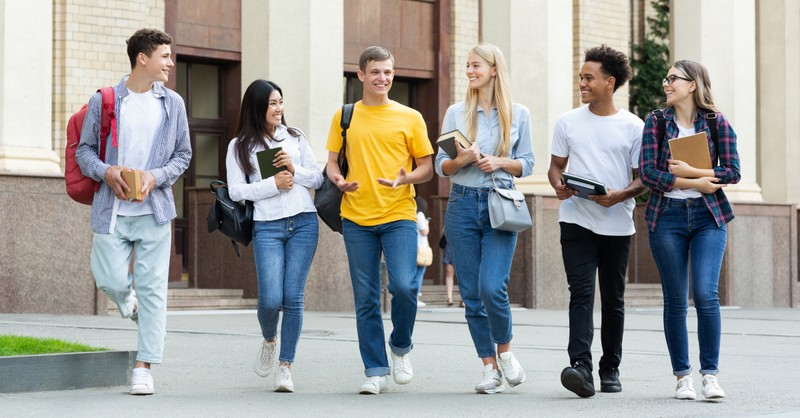 diverse group of college student friends walking together