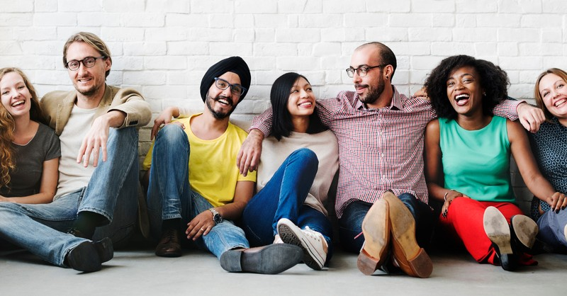 multicultural diverse row of friends sitting against wall arms over shoulders smiling