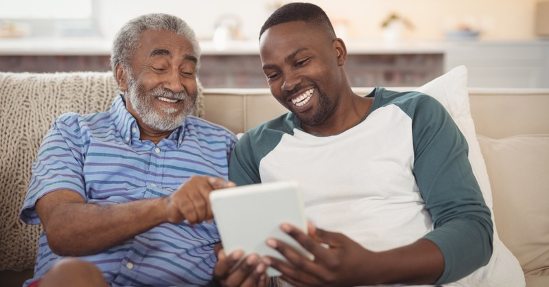 grown son with senior dad laughing on couch with ipad Fathers Day