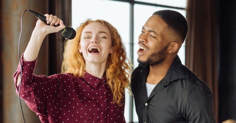 woman and man singing joyfully into microphone worship