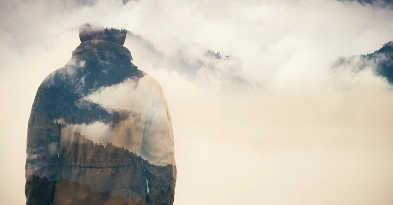 Man silhouetted by clouds and mountains