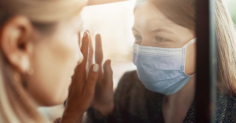 two women looking through window wearing face masks