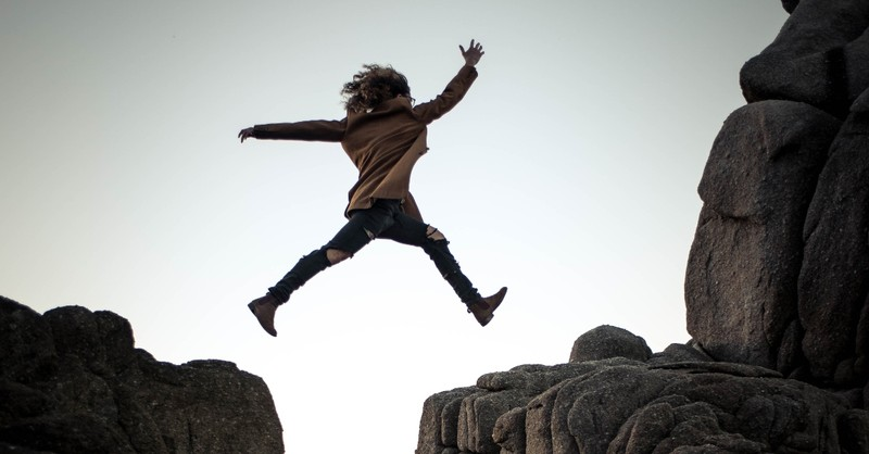 woman jumping over a rocky chasm
