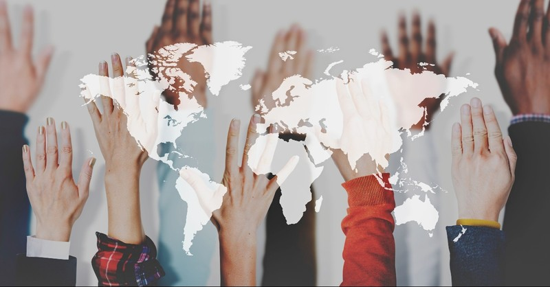 Hands of all races raised in front of a map of the world