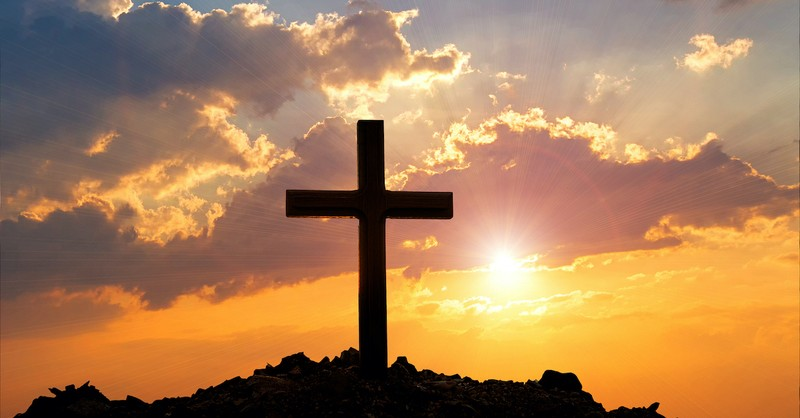 silhouette of cross against sunset background, expiation and propitiation