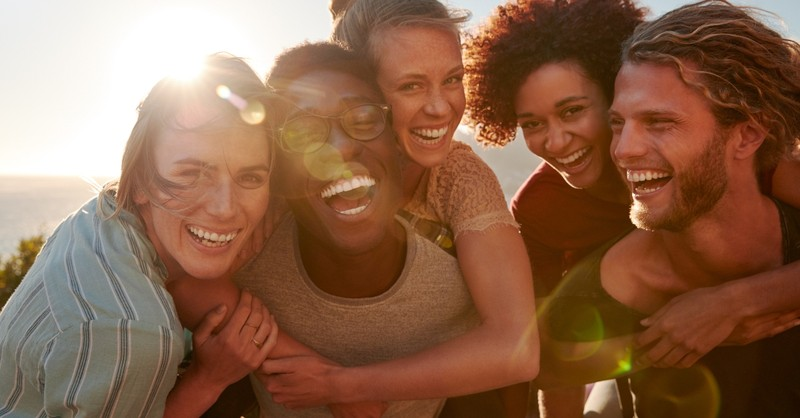young group of friends laughing together with sun setting, lifelong frienship