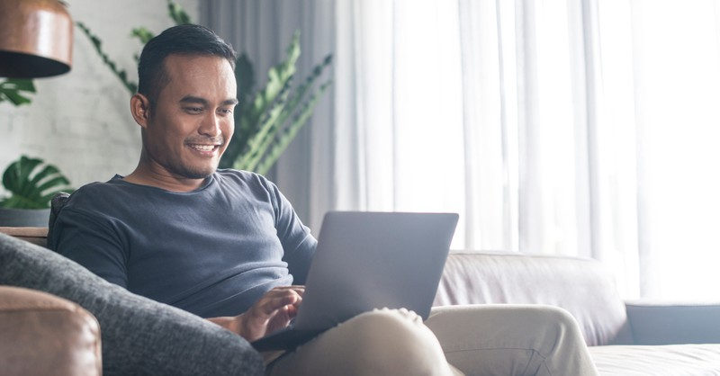 man happy on couch on laptop