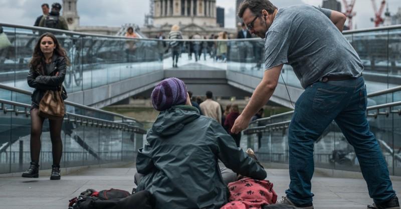 man giving to homeless beggar on street