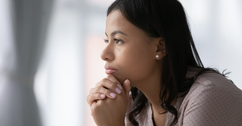 woman deep in thought gazing out window