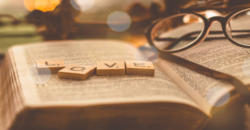 love scrabble pieces on open book with glasses