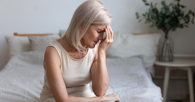 senior white woman looking ill or in pain sitting on bed