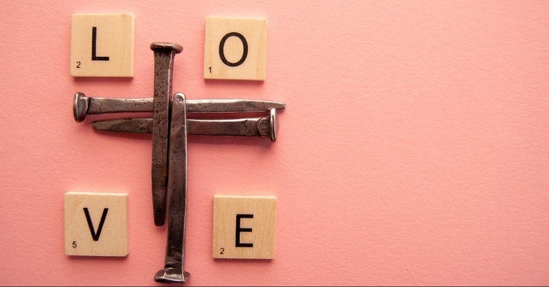 nails in shape of a cross with scrabble tiles spelling love