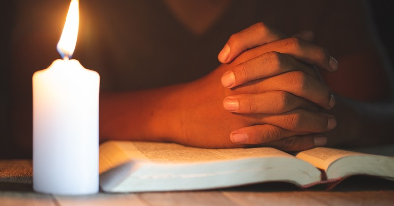 hands together praying over bible with lit candle, christians prayer closet