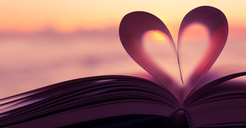 open book with pages folded into heart shape at sunset healing