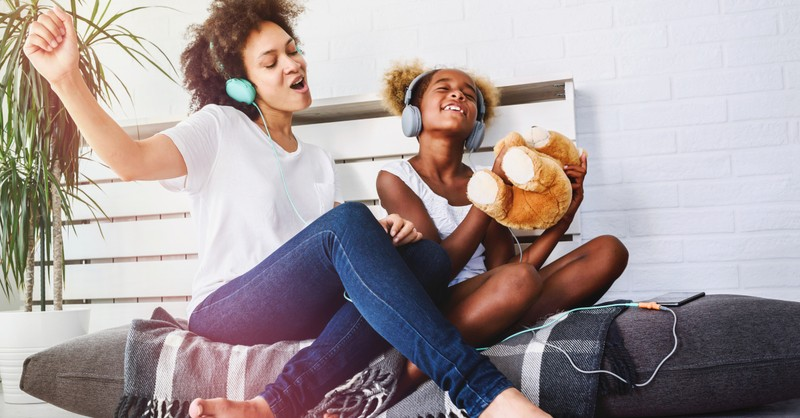 joyful mom and daughter singing praise songs with headphones on