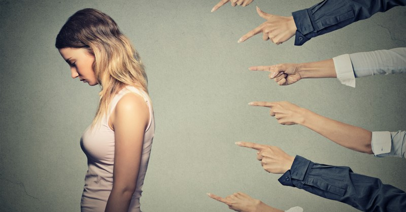 Hands pointing at a disappointed woman, the difference in judging to love and judging to shame