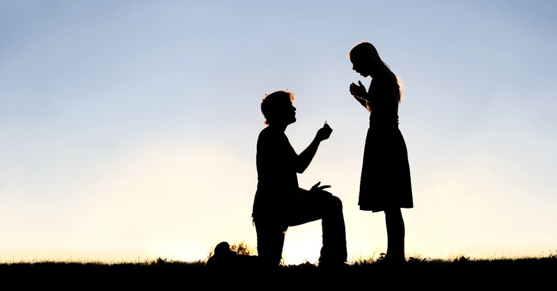 silhouette of man on knee asking woman to marry him