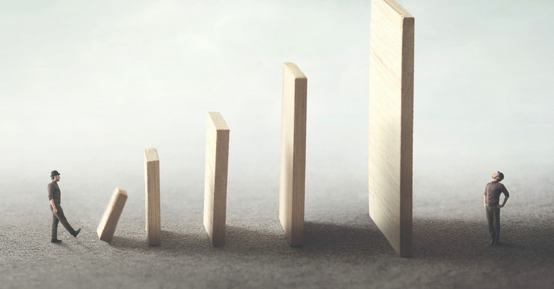 man knocking domino which will flatten man on other end blind leading the blind