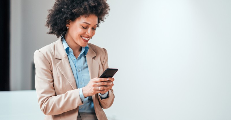woman smiling at Instagram social media on phone