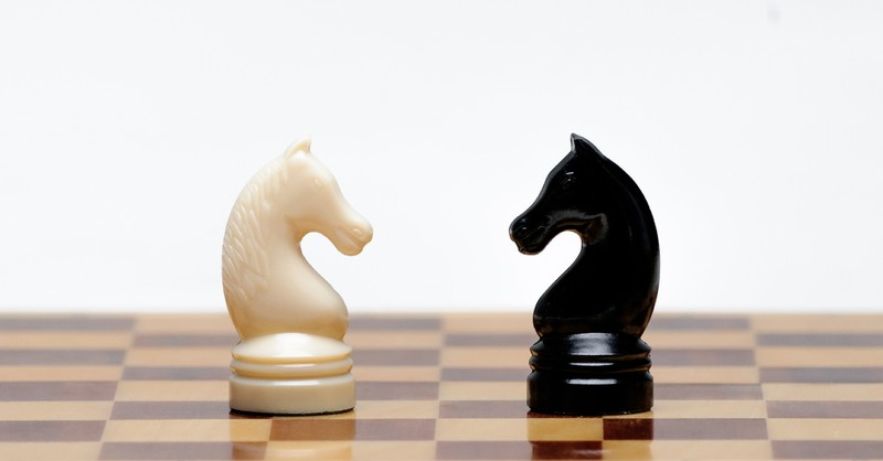 black and white chess pieces on chess board facing eachother