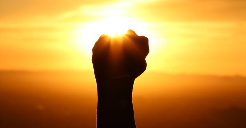 fist raised before sunset
