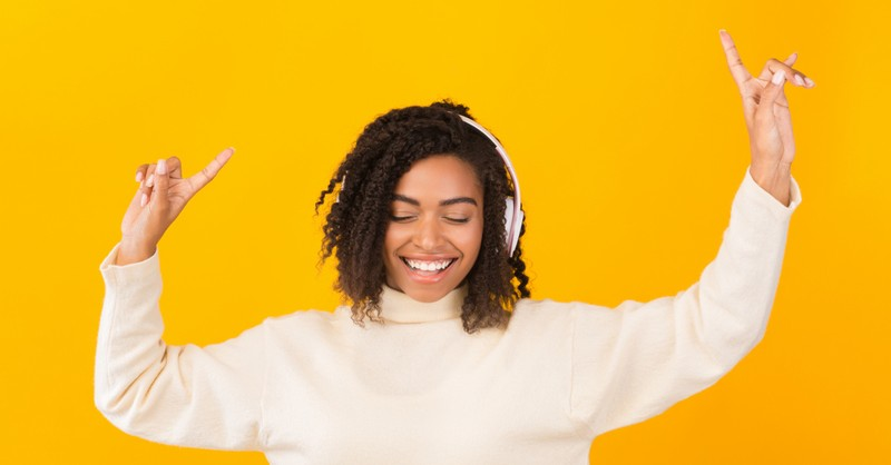 woman with headphones signing to praise music worship pointing up
