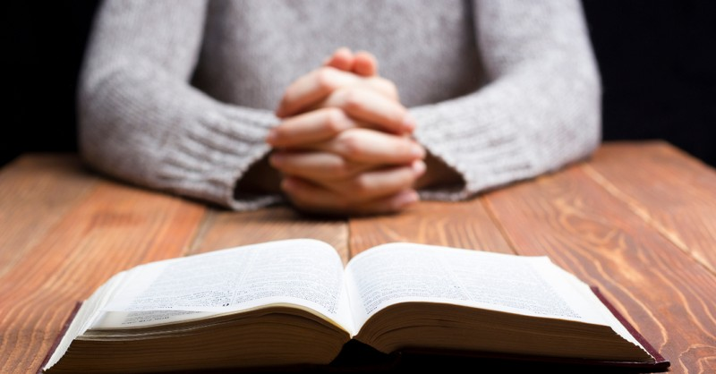 woman folding her hands by the bible