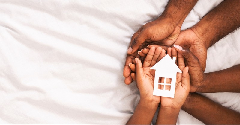 Hands of a father, mother, and child holding a paper house together