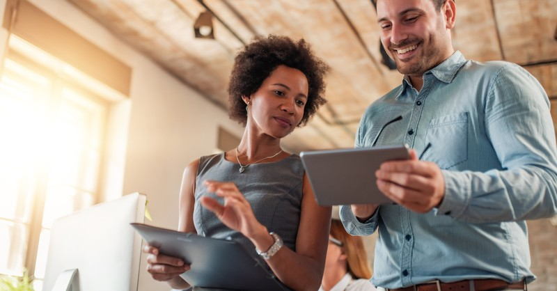 diverse man and woman at work on touchpad screens