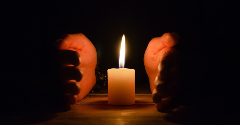 hands cupping candle flame hedge of protection