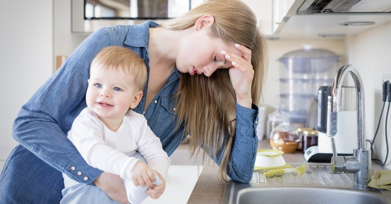 stressed mom with child on hip in kitchen