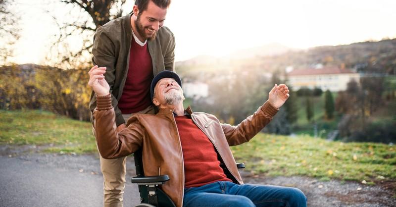 man pushing senior in wheelchair outdoors smiling