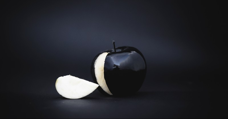 A black apple with a black background - false prophets in the bible