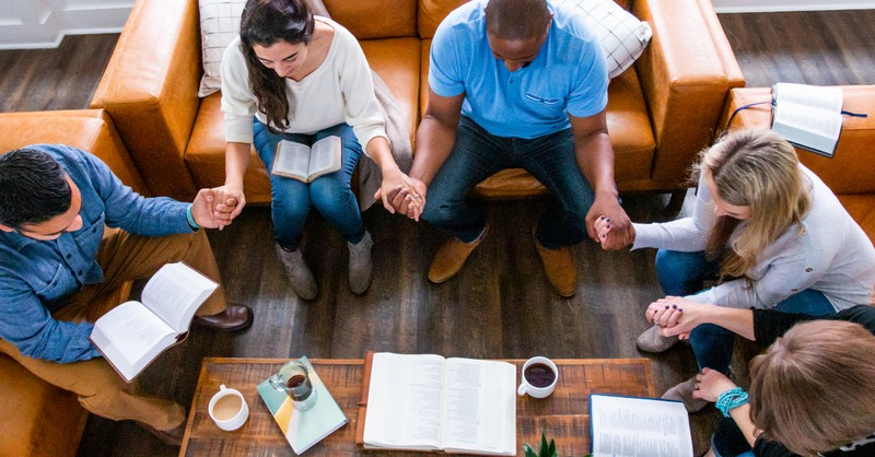 bible study friends holding hands praying for a hedge of protection