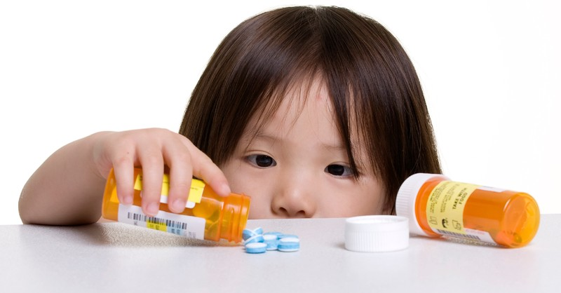 little girl playing with pills