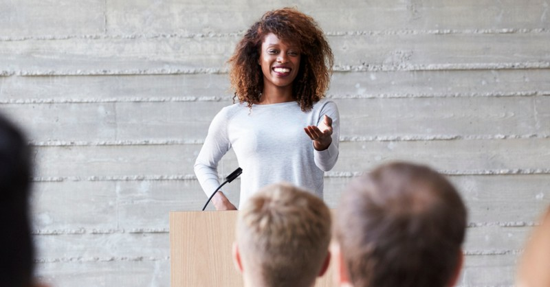 woman public speaking at podium with microphone