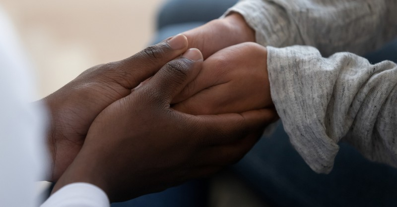 holding hands offering peace in injustice