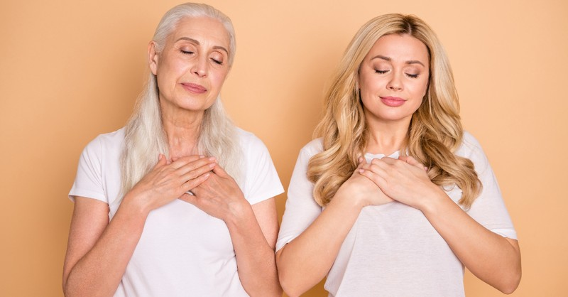 mom and grandma praying next to eachother against orange background